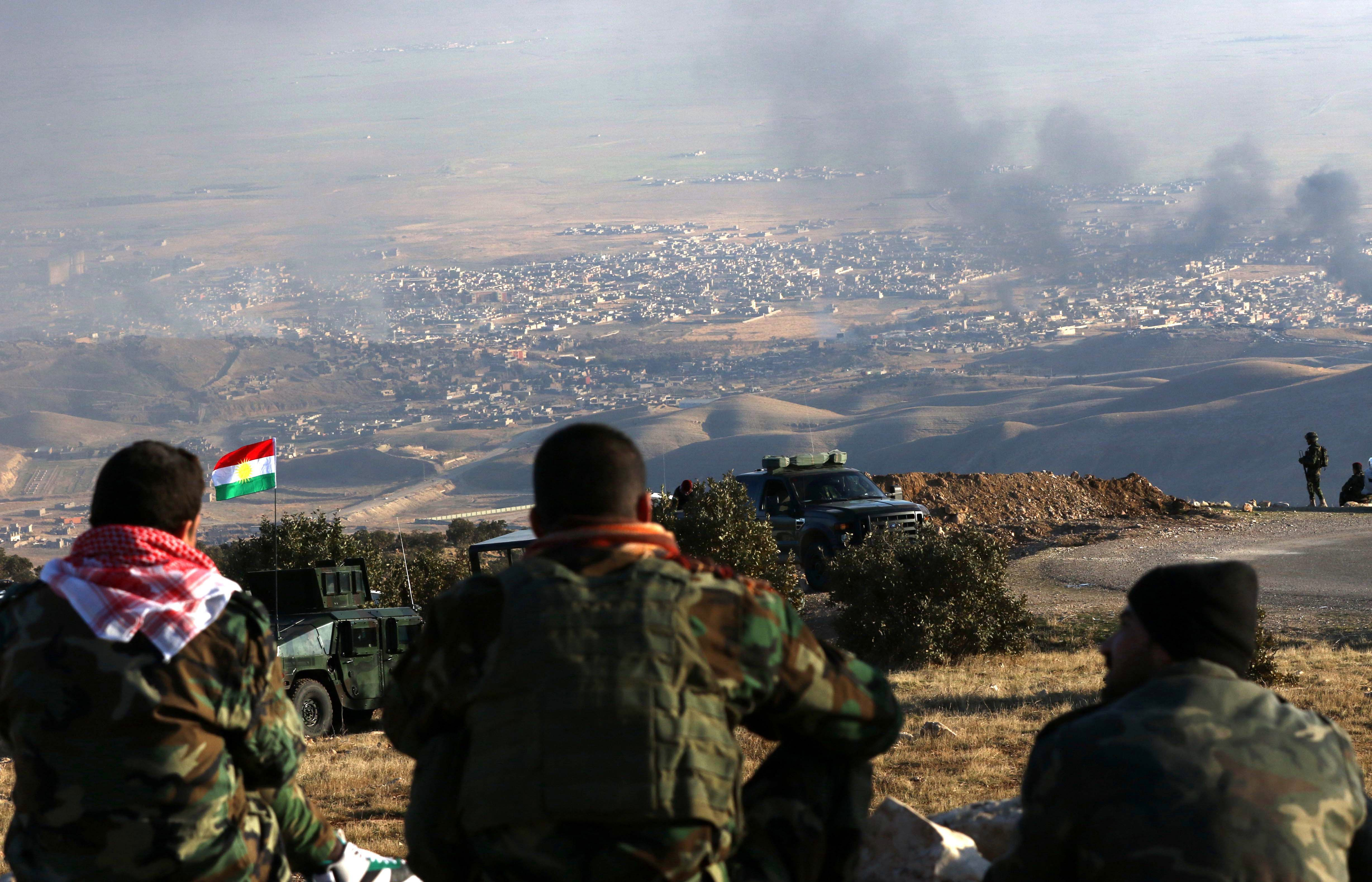 Kurdish fighters look on as smoke billows from Sinjar, in northern Iraq, during an operation, backed by U.S.-led strikes, against the Islamic State group on Thursday. Safin Hamed/AFP/Getty Images